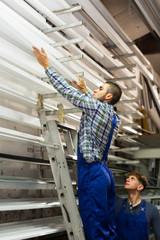 Two workers choosing PVC window profile