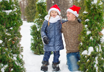 Adorable little girl and happy dad in Santa hats outdoors
