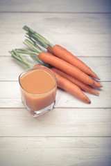 carrot juice and carrot segments on a wooden background