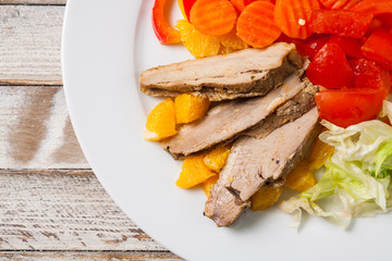 Roast duck slices with orange and vegetables, closeup