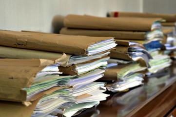 piles of paper folders on a desktop