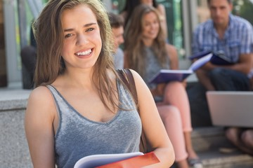 Pretty student smiling at camera outside