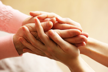 Old and young holding hands on light background