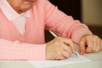 Hands of adult woman writing with pen,