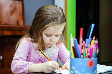 Cute little girl studing to speaking and writing letters at home