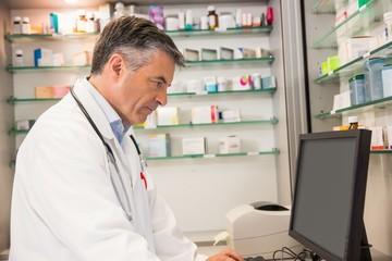 Focused pharmacist using the computer