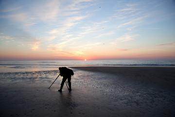 photographer alone on beach at sundown in holland