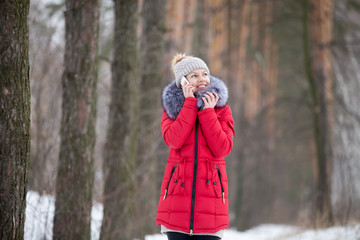 Happy smiling female in red winter jacket talks on mobile phone,