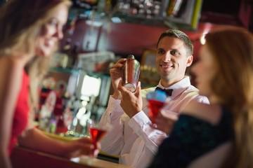 Handsome barman chatting to customers
