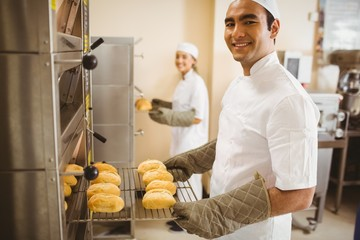 Baker smiling at camera taking rolls out of oven