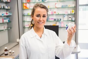 Junior pharmacist holding medicine jar