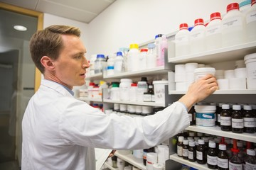 Handsome pharmacist taking medicine from shelf