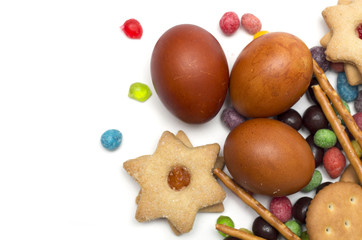 Happy Easter. Easter eggs with candy and cookies. Photo.