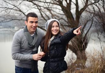 Happy couple enjoying outside and pointing