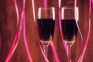 Two wineglasses with red wine over abstract background