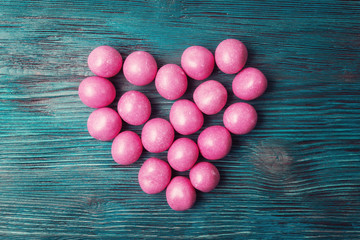 Sweet pink candies on Valentines day over vintage wooden backgro
