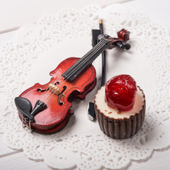 Chocolate candy and musical violin on the table