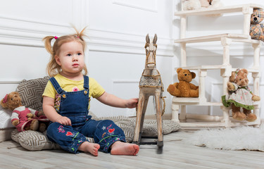 Little girl sitting surrounded by toys