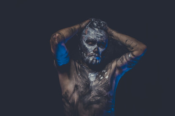 muscular naked man covered with paint and mud skin