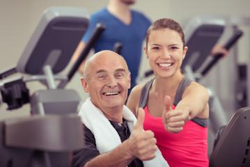 senior-kunde und trainerin zeigen daumen hoch
