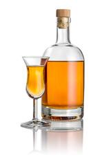 Flasche und hohes Kelchglas mit bernsteinfarbener Flüssigkeit
