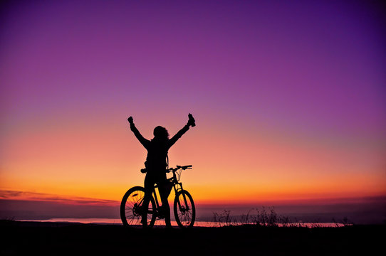Girl with a bicycle watching the sunset