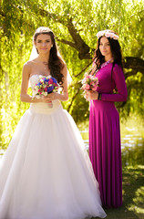 brunette bride posing with bridesmaid in long dress posing at pa