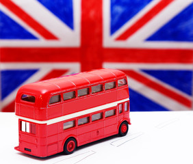 a red double Decker bus and flag