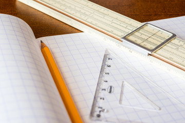 Schemes the pencil and triangle with slide rule on the table