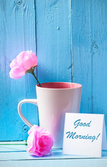 Mug with roses on blue wood background with good morning text