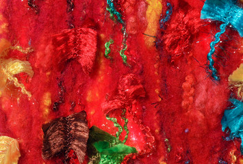 colored shiny thread on a red textured fabric