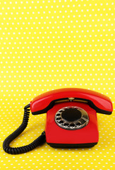 Red retro telephone on bright background
