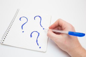 hand draws question mark in the notebook pen