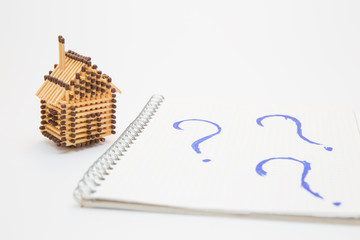 matchbox house and notebook with picture of question marks