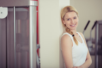 lächelnde blonde frau im fitnessraum