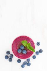 blueberry milkshake in a glass on white wooden table, vertical