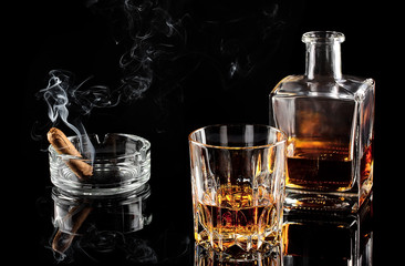 Glass of whiskey with ice, and a carafe of steaming cigar