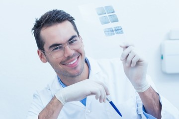 Smiling male dentist holding at x-ray