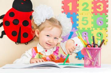 Cute child girl drawing with pencils iin kindergarten