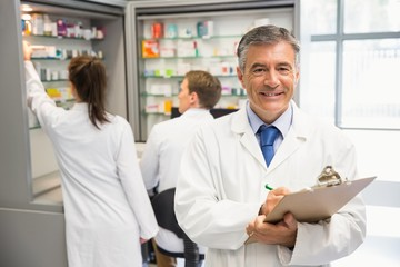 Senior pharmacist writing on clipboard