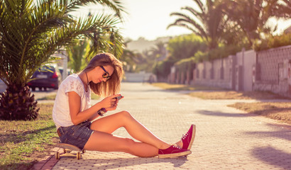 Young girl with skateboard and smartphone sitting outdoors on