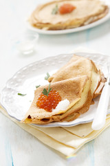 Pancakes with caviar, sour cream and parsley