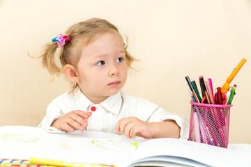 Cute child girl drawing  in preschool at table in kindergarten