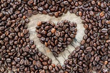 coffee beans in heart shape on wood background