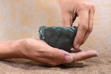 women's hands molded from clay a cup