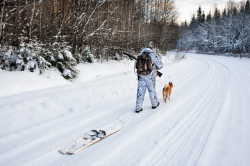 the hunter pulls the skis on winter road
