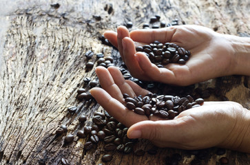 Coffee beans in hands on wooden background