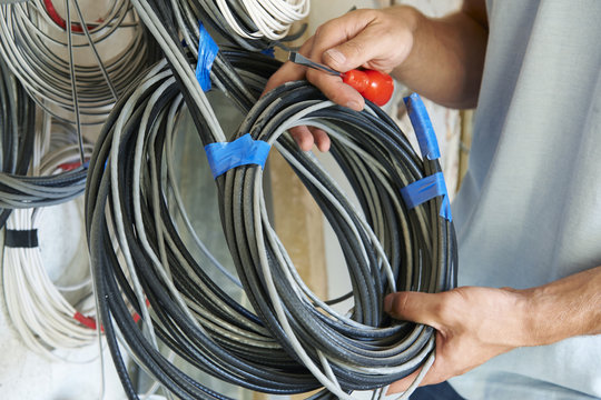 Close Up Of Electrician Fitting Wiring On Construction Site