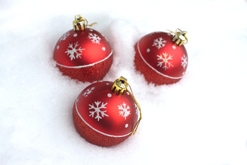Red Christmas balls with painted snowflakes lying in white snow