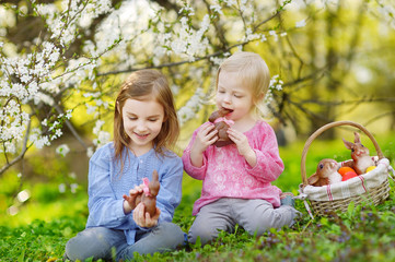 Two girls eating chocolate bunnies on Easter
